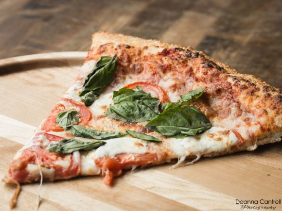 Slice of vegetarian pizza on a wooden tray.
