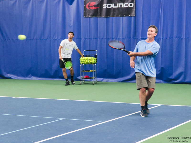 A man hits a tennis ball under the guidance of a pro instructor.