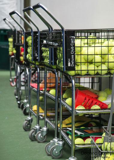 Tennis balls in carts ready for practice on the courts.