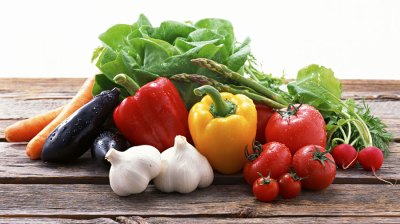 Image of fresh real food, including carrots, peppers, tomatoes, spinach, and garlic