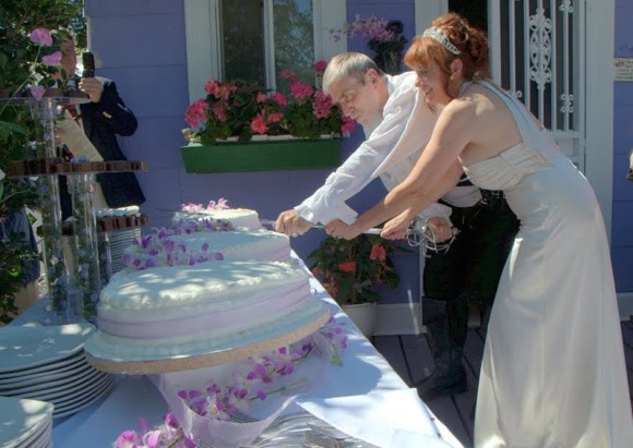 Bride and groom cutting wedding cake with a sword.