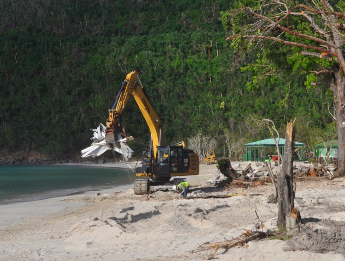 An earth-mover scoops up a load of debris at Magens Ba7.