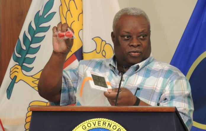 Gov. Kenneth Mapp demonstrates a solar light donated by the V.I. Humanitarian Relief Fund. (Jamie Leonard photo)