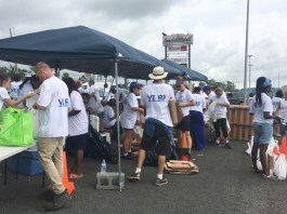 Volunteers hustle to hand out supplies and keep the line of cars moving quickly at Saturday's VI-R3 event.