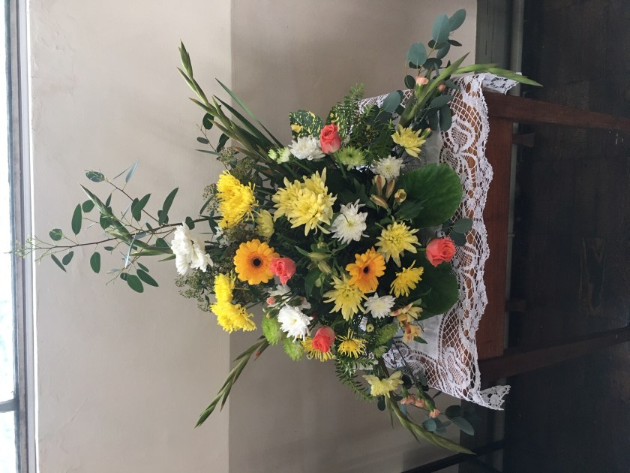 flower arrangement by the memorial book. Yellows, pinks.