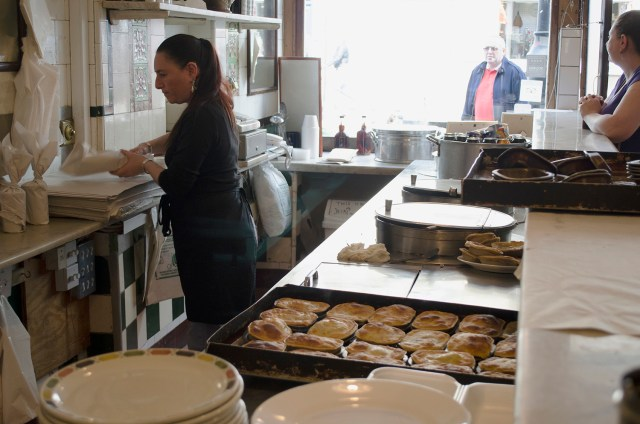 A large order is wrapped to take away while the hot pies, fresh from the oven, cool on the counter