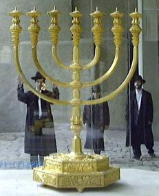 Three Hasidic Jews look upon a Menorah Replica