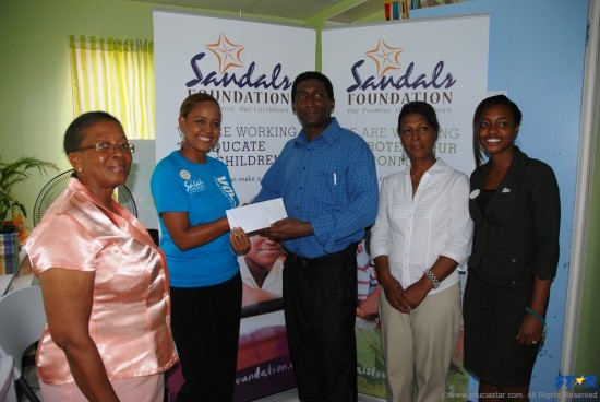 Public Relations Manager for Sandals Saint Lucia Rhonda Giraudy Presents the Sandals Foundation's financial injection to the ACES program for the first school term of 2014 to the vice president of the Saint Lucia Crisis Center.  They are flanked by other representatives from both organizations.