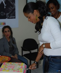 Birthday girl Marcia digs into her cake while  colleagues look on expectantly.