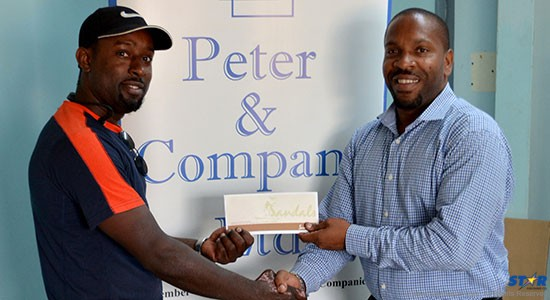 Good son Staron Oculi receives his prize from    Germaine Serieux of Peter & Company.