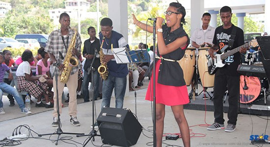 This student belts out a song as the school band plays on.