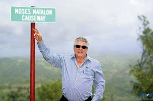 Sandals Chairman Gordon Butch Stewart stands next to the sign renaming the Pigeon Island Causeway in Saint Lucia.