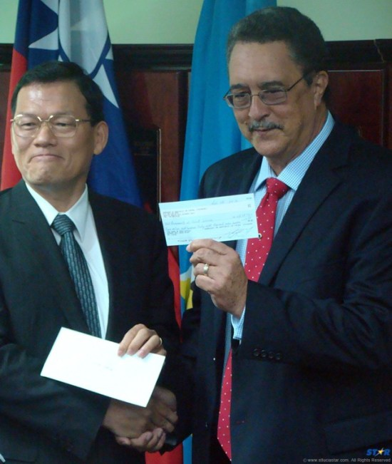 Prime Minister Kenny Anthony (right) accepting a couple more checks from the current Taiwanese Ambassador David Chang.