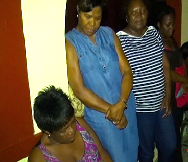 Family members grieving over the brutal slaying of Oswald Downes.