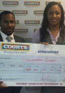 Daarsrean Greene (left) accepting his grand prize of $8,000 from Britney Jongue of Unicomer.