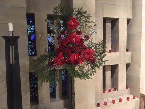 Red flower arrangement in a church setting.