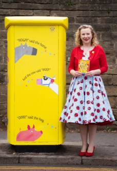 Woman holding a book stood next to a brightly painted postbox