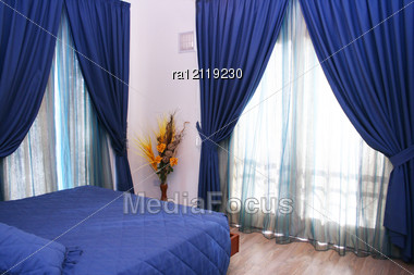 bedroom with blue curtains and bedspread - stock photo ra12119230