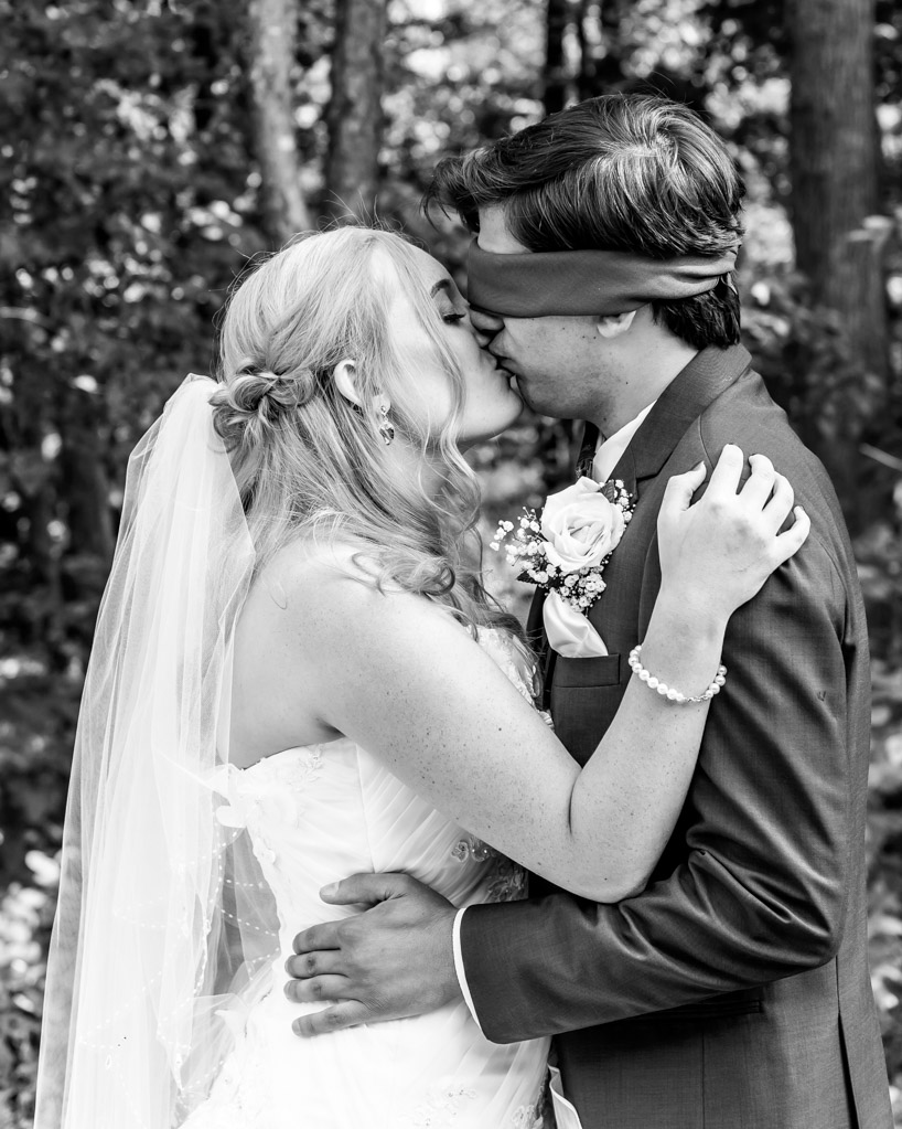 Bride And Blindfolded Groom Kiss During First Look