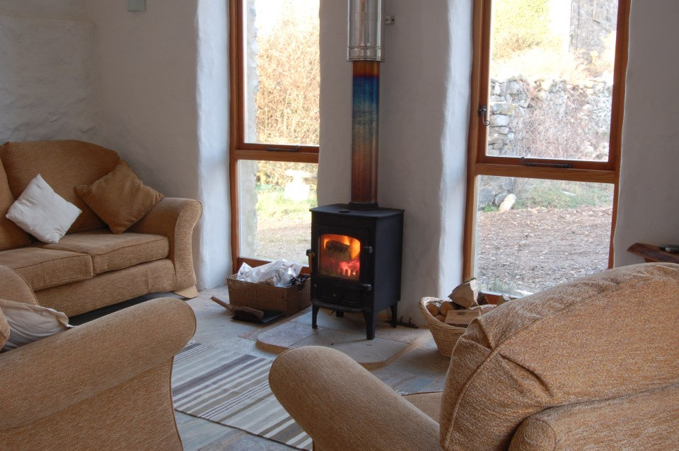 Harmony Barn sitting room. A cosy eco holiday cottage with its blazing log burning stove at Stones Cottages.