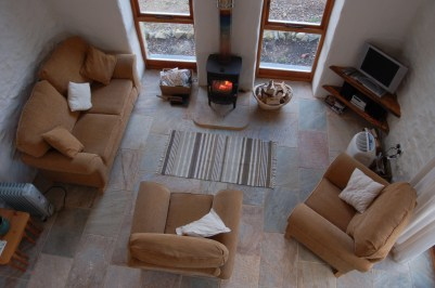 Pembrokeshire Holiday Cottages Harmony Barn, a cosy eco holiday cottage - Sitting Room from the balcony with blazing log burning fire.