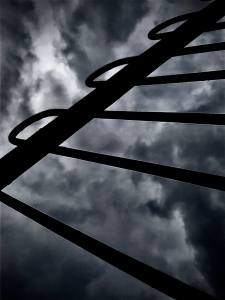 A spooky, dramatic photograph of a metal gate against the stormy sky.
