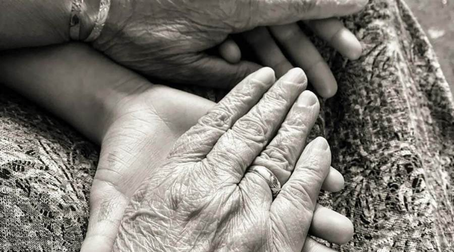A loving black-and-white photograph of wrinkled hands clasping young ones.