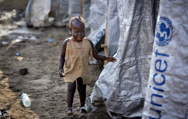 A young displaced girl starts crying after the relative she was with disappears into a row of latrines, at a United Nations compound. (AP Photo/Ben Curtis)
