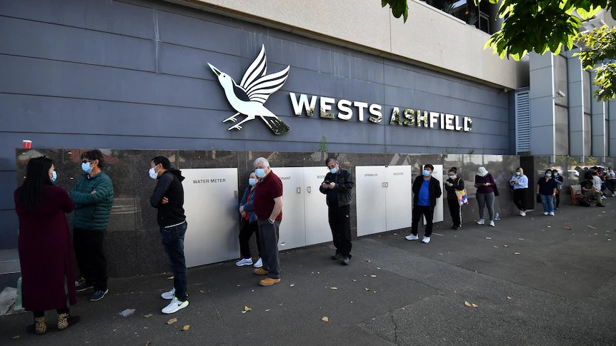 people in masks lining up outside a building reading wests ashfield