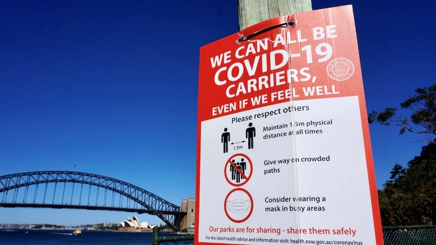 A COVID-19 sign on a pole next to Sydney Harbour.