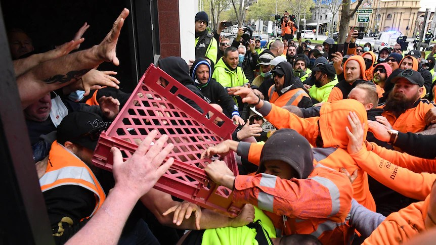 Protesters throw a milk crate at security