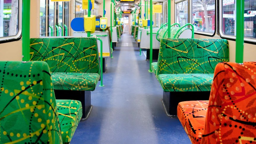 An empty tram with colourful green and orange seats, in daylight.