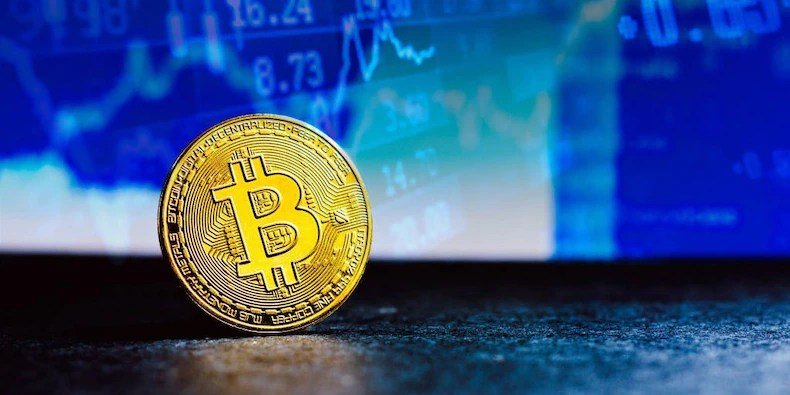 A gold Bitcoin seen on display with a stock market graph in the background
