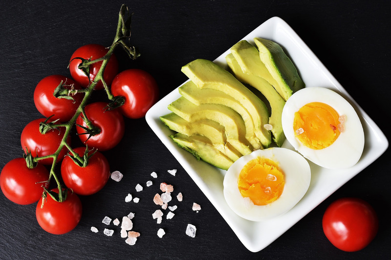 A plate with hard boiled eggs and avocado with tomatoes on the vine and seasalt on the side. Small changes lead to 17 pound weight loss.