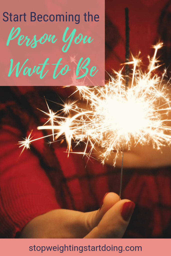 A girl in a red coat holding a sparkler. Start becoming the person you want to be.