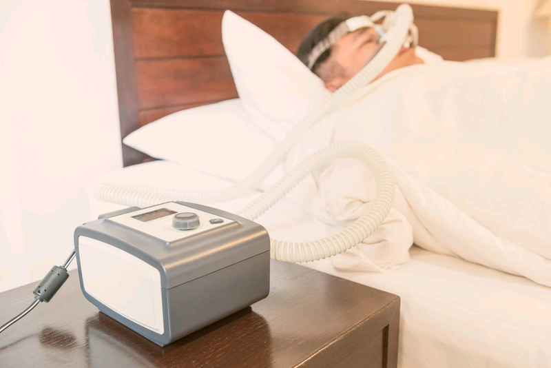 A CPAP machine hooked up to a man in bed. Why CPAP can save your life.