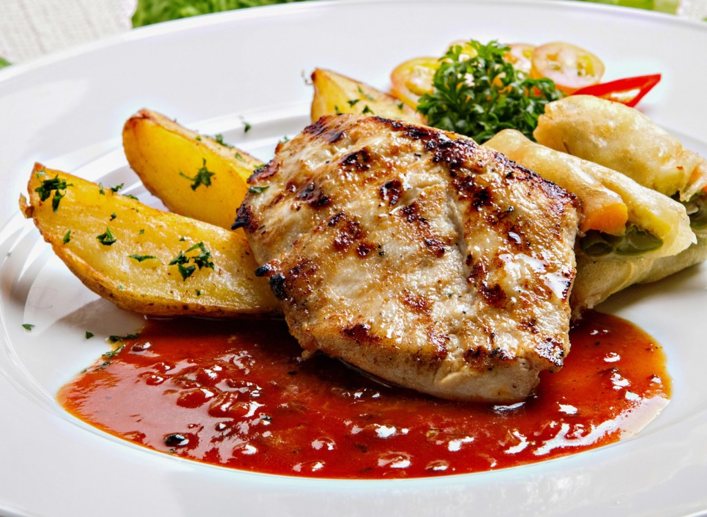 Chicken breast and potatoes in a red sauce on a white plate. Soft foods diet