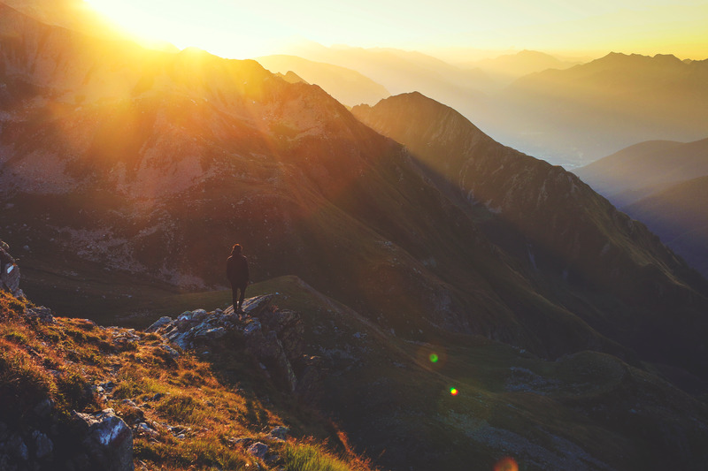 A person standing on a mountain summit at sunset. Start becoming the person you want to be.