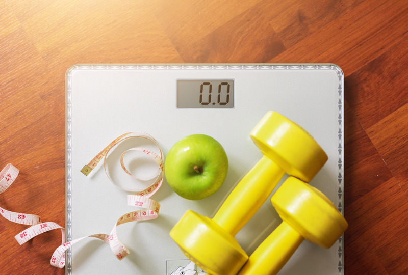 A scale with an apple, tape measure, and hand weights on it. A look at my 36 pound weight loss.