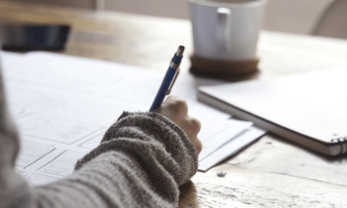 The arm of a woman in a sweat writing and filling out forms with a cup of coffee. | Filling out the bariatric pre-visit paperwork | Facing your Obesity Issues