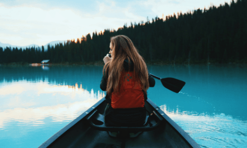 A woman in the front of a canoe on a lake surrounded by trees. The Benefits to Bariatric Surgery | Bariatric Surgery Transforms Your Life