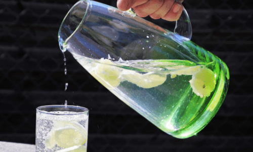 A glass pitcher with water flavored with lemon and mint pouring into a glass. Six Easy Ways to Drink More Water | Tips for Reaching Your Fluid Goals