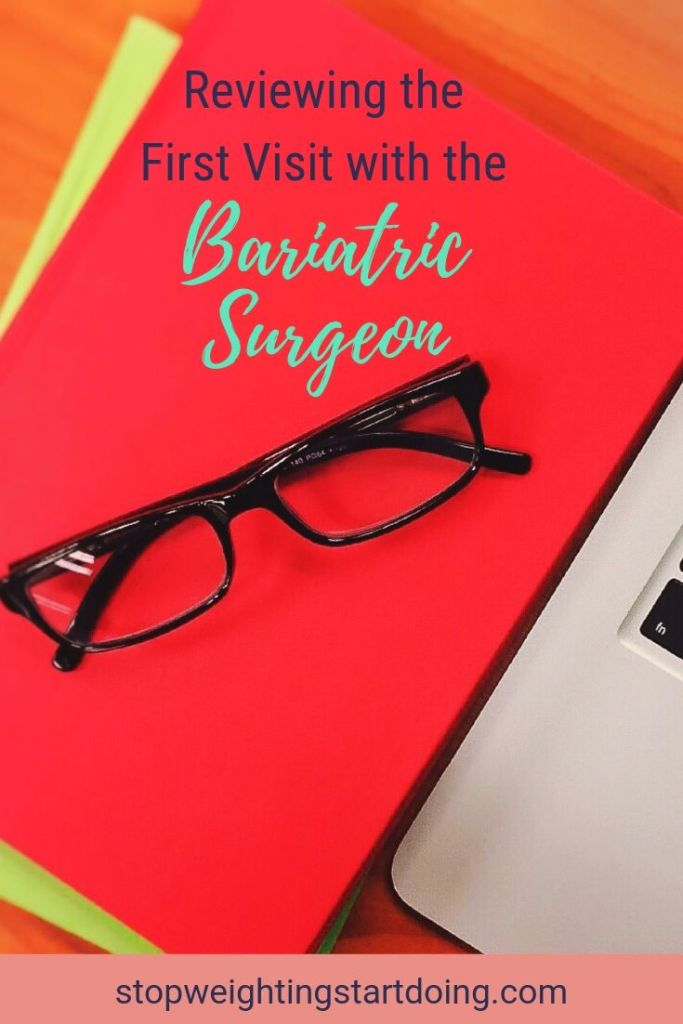 a pair of black reading glasses on a red notebook next to a silver laptop. Reviewing the first visit with the bariatric surgeon.