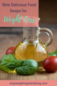 A glass bottle of olive oil surrounded by basil leaves and cherry tomatoes. Nine delicious food swaps for weight loss.