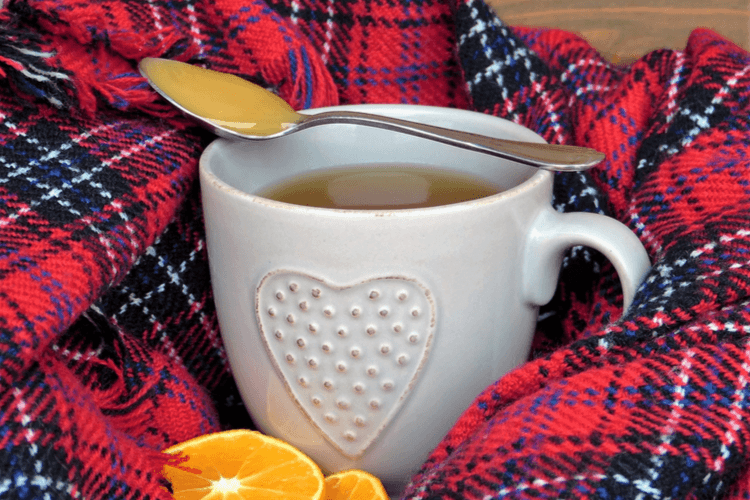 A cup of hot team wrapped in a scarf with orange wedges and honey. 7 Practical Ways of Staying Warm After Losing Weight | Free Printable! | 20 Ways to Stay Warm Featured Image