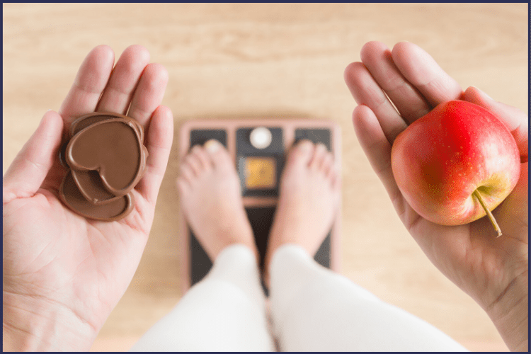 A woman standing on a scale holding chocolate hearts in one hand and an apple in the other hand. How to Stay Motivated to Lose Weight During a Crisis | Murphy's Coming | Image | how to stay motivated on a diet, motivation