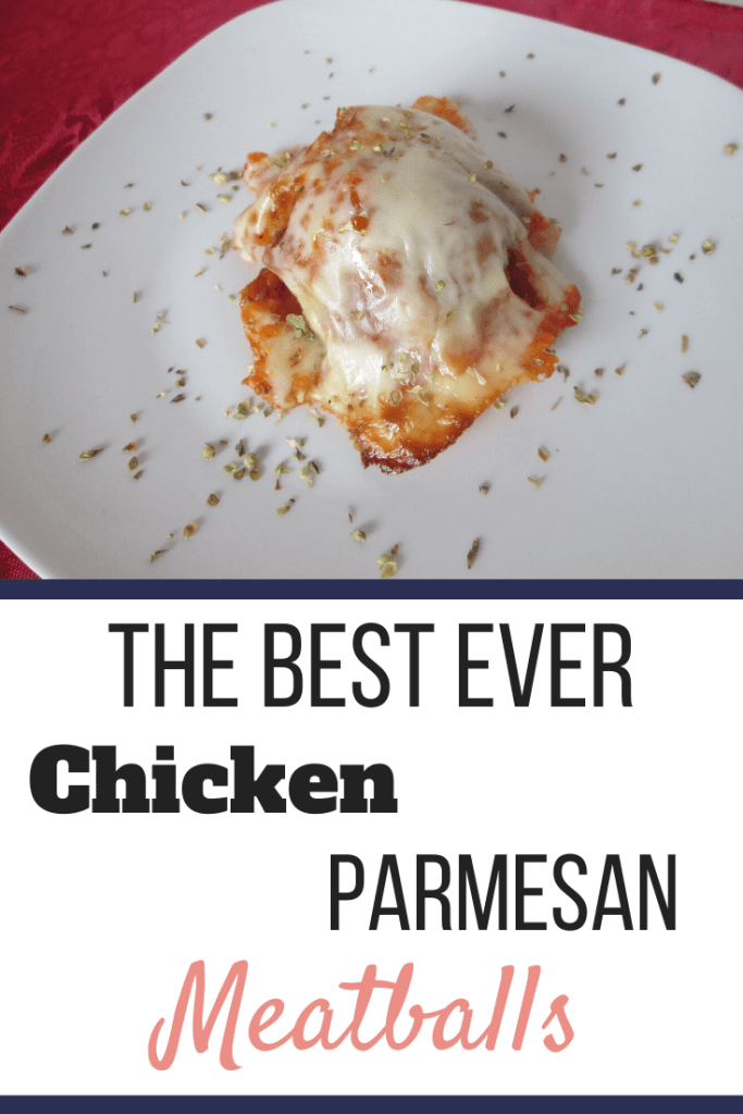 A chicken parmesan meatball on a white plate with oregano sprinkled on top. | The Best Ever Chicken Parmesan Meatballs Recipe | Soft Foods Stage | Featured Image | Chicken Parm Meatballs