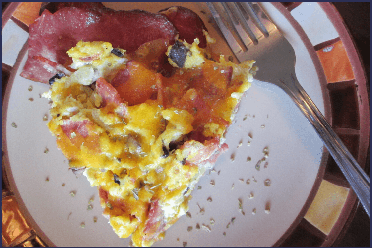 A slice of turkey bacon, egg, and cheese pie on a plate next to a fork. This Turkey Bacon, Egg and Cheese Pie Will Blow Your Mind! | Bariatric | Image | turkey bacon calories, breakfast pie