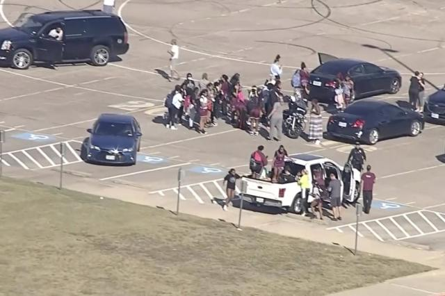 In this image from WFAA-TV video, students evacuate Timberview High School on Wednesday, Oct. 6, 2021 in Arlington, Texas. Authorities say a student opened fire inside the Dallas-area high school during a fight. (WFAA-TV via AP)