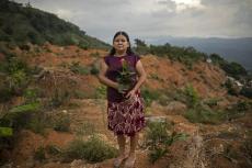 Olga Ondina, de 52 años, posa para un retrato en el lugar donde estuvo su casa antes de ser destruída por un deslave tras el paso de los huracanes Eta e Iota en la comunidad de La Reina, Honduras, el miércoles 23 de junio de 2021. (AP Foto/Rodrigo Abd)